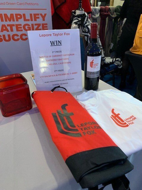 Wine, a backpack, and a t-shirt on a table available as a prize.