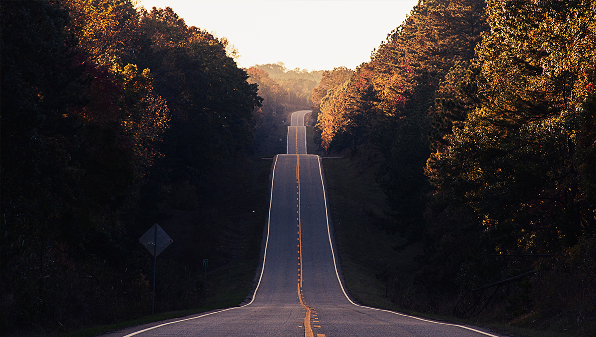 A road at sunset rolling over steep hills.