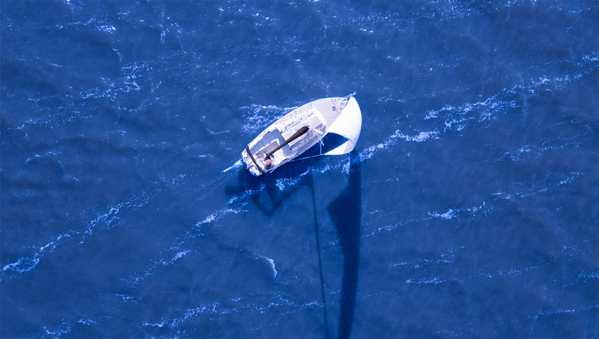 A bird's eye view of a boat in the middle of vast, blue waters